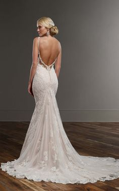 This lace over matte-side Lustre satin fit-and-flare designer wedding gown from Martina Liana offers a sexy deep V neck and flirty peek-a-boo back, intricate pearl beading, and lace detailing throughout. The back zips up under crystal buttons.