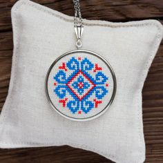 Cross stitch necklace with blue and red ethnic embroidery