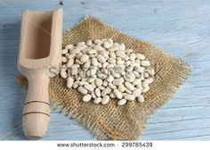 Wooden scoop with white beans on old table - stock photo