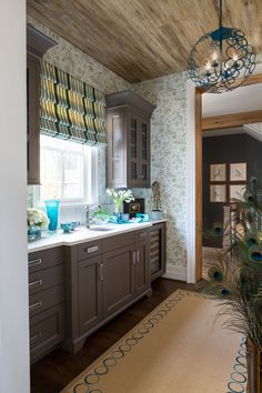 Margery Wedderburn transformed the butler's pantry with bright, vibrant green, peacock, and cyan blue colors. The ceiling is actually a wallpaper, not the repurposed pine it appears to be. [Photo via Angie Seckinger]