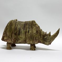 Rihino, a ceramic sculpture. Handbuilt with light rough chamotte clay. Covered with glaze . Electric high-fired at 1060 C degree. Height: 6 / 16 cm. Length: 11 / 34 cm.