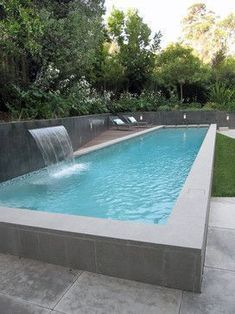 A raised lap pool with a water fall is the main feature of the back yard. The raised edge works as a seat wall and helps mitigate the height... #modernpoolhall
