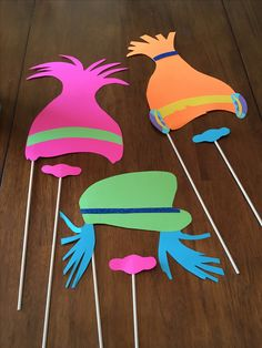Trolls party photo booth props made from Michaels crafts cardstock paper. Kids can stick glitter flower stickers onto Poppy's hair bandana.