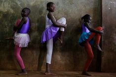 Young ballerinas dressed in leotards and tutus stretch their legs before a lesson