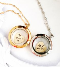 A small glass encasement for the brass heart inside, this locket holds a small charm stamped with two initials and an arrow. The round locket allows the heart to float freely inside and can be opened to add other small charms, glitter, beads or even bits of flora.