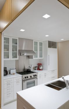 We love the kitchen's bright, modern finishes. The cabinetry is custom made of white lacquer with pre-finished maple interiors, and white glass countertops are sourced from SMC Stone in Brooklyn.