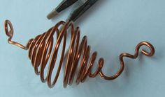 Bending a copper wire spiral cage for floral art. Curl the two straight wires at either side. Copper Wire Crafts, Copper Jewelry, Wire Jewelry, Jewellery, Rain Chain Diy, Rain Chains, Copper Silverware, Nest Design, Wire Art