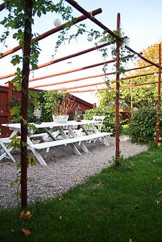 Contemporary pergola, inspired by hop poles and painted in the traditional Falu red, Sweden