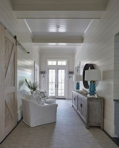 The bedroom hallway is filled with a shiplap wall lined with white slipcovered chairs...Coastal Styling.