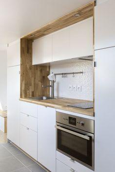 Cuisine blanche avec encadrement et plan de travail en bois. Intégrer des rangements en hauteur : idéal pour aménager une petite cuisine lumineuse ! #cuisine #aménagement #bois #blanc #petitecuisine #RHINOV