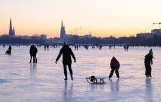 Abendliches Alstervergnügen auf dem Eis der Hamburger Außenalster. Hamburg Panorama mit Kirchtuermen. Bilder von Hamburg. 256_5942 Die zugefrorene Alster für die Hamburger ein Volksfest. Bis in den späten Abend wird auf dem Alstereis Schlittschuh gelaufen oder geschlendert