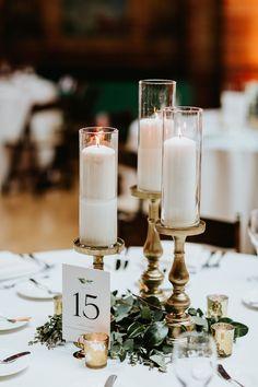 Stunning candle stick centerpiece for awedding with greenery. Table numbers and mercury glass votive candles. Stick Centerpieces, Candlestick Centerpiece, Greenery Centerpiece, Candle Wedding Centerpieces, Reception Decorations, Mercury Glass Centerpiece, Mercury Glass Wedding, Graduation Centerpiece, Floral Centerpieces
