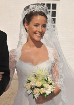 On May 24, 2008, HRH Prince Joachim of Denmark married Miss Marie Cavalleri. The striking Parisian bride wore an off-white gown with a 10 foot train from the fashion house Arasa Morelli. Marie's tulle veil with a lace border was held in place by a diamond tiara lent to her by the groom's mother, Queen Margrethe,  and it featured sweeping designs with pave set flowers.