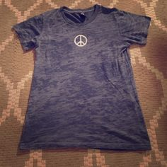"""Crackled blue peace sign t-shirt Crackled blue t-shirt with a white peace sign on the front. The shirt is in """"like new"""" condition and is 50% cotton and 50% polyester. The shirt is meant to be form-fitting and has some stretch in it. Alternative Apparel Tops Tees - Short Sleeve"""
