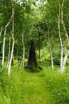"""[i]Birch trees surround a conical sculpture. [/i]  Like this? Then you'll love  [link url=""""http://www.houseandgarden.co.uk/outdoor-spaces/features/five-trees-and-shrubs-for-autumn-colour""""]5 Trees and Shrubs For Autumn Colour[/link]"""