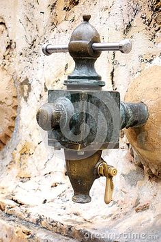 A closeup image of a very old town water spigot made of brass and copper in the town square of Tarragona Spain.