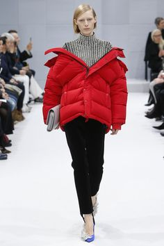Balenciaga Fall 2016 - Demna Gvasalia's red puffer is the coat that ruled 2016. Worn with a bejeweled turtleneck on the Balenciaga runway, the off-the-shoulder jacket spurred a trend for wonky outerwear.