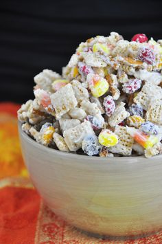 A new twist on party snack mix includes white chocolate, chex cereal, fall M&M's, candy corn, and pretzel sticks for a Halloween party or fall treat.