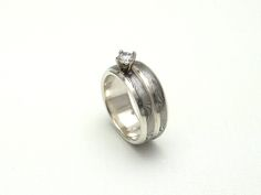 http://www.jloose.com/siteimages/sankey.c.2.15.15.jpg A handmade, sole-authored engagement / wedding band in stainless damascus, fused together to look as one, in Sterling silver and with a prong-set diamond.