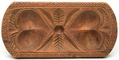 "This rectangular butter print is carved with double hearts connected by a feather or leafy branch detail. The shaped edge features a crosshatch carved border and gouge-carved decoration above each heart form. The piece displays its original dry surface and measures 3¼"" x 6½"" on its face and is 4¼"" high overall with the handle. This butter print brought $2070"