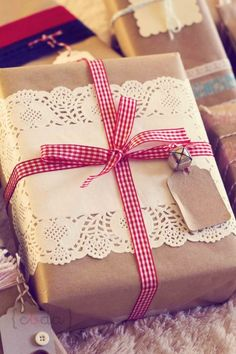 Gift wrap decorated with lace, a ribbon of red and white squares and a bell.