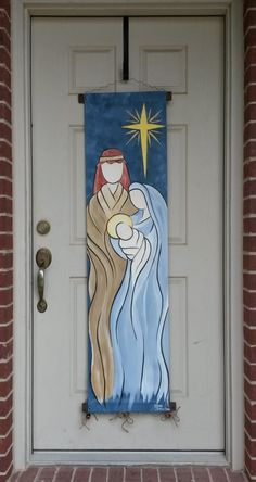 The Holy Family is the perfect Christmas greeting to those who enter your home or office! This simplistic watercolor style canvas door decor measures 15W X 60 L. It is suitable for hanging on an interior or exterior door or wall.  Hand painted with acrylic paints on 100% cotton canvas and embellished with silver and gold glitter puff paint to add that little touch of shimmer to the star and halo! Canvas is wrapped at the top and bottom edges around a 17 wood and wire display hanger and…