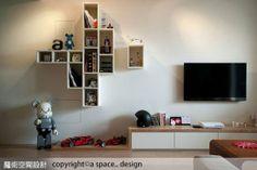 客廳主牆利用格櫃交錯的設計方式,形成焦點所在,建立收納、展示機能。