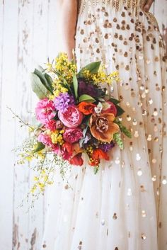 A gold-dusted dress and a bouquet of bright flowers.