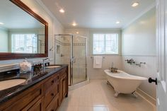 Ensuite bathroom with claw tub and standup shower with his and her sinks