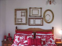 oval and rectangular empty frames, in brown and gold, arranged on a white wall, near brown wooden bed, with red and white pillows and covers