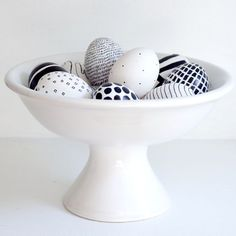 Putting a few of the colorfully painted eggs into a raised candy bowl would make a great start to a simple modern design centerpiece.