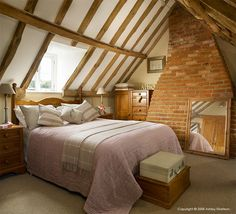 Attic bedroom in a wooden beamed cottage in Oxfordshire.