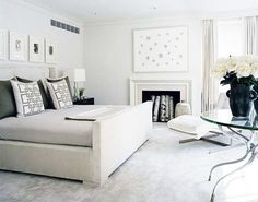 Modern light gray bedroom with upholstered bed, graphic toss pillows, art, grommet drapes and glass table. http://cococozy.com