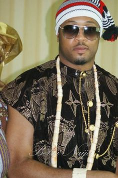Traditional Igbo (Nigeria) men's wear.  Trademark is red/white/black hat and printed  velvet top