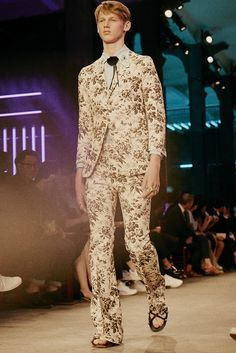 Spotted on the runway at the Gucci men's Spring Summer 2016 fashion show, a black herbarium suit detailed with a flower necktie designed by Alessandro Michele.