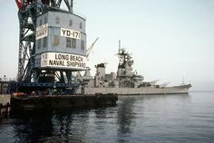 The battleship USS NEW JERSEY (BB-62) is visible behind a floating crane (YD 171) at the Long Beach Naval Shipyard. All Hands - May 1983