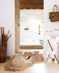 A large rock in the entryway of a crisp and white bedroom