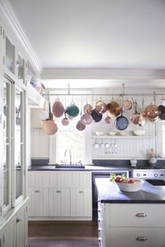 For extra storage space, hang pots and pans from the ceiling. | http://domino.com