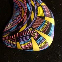 101, galet peint à l'acrylique dans les tons rose, mauve, bleu, lie de vin, jaune, doré et noir