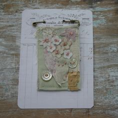 these beautifully individual brooches are created using snippets of antique fabrics, papers, buttons, threads and beadsbacked with antique homespun french textile and a hand stitched 'ac'the banner hangs from a kilt pinmeasures approx 5.5 X 9cmswas $28 now $20