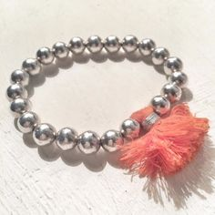 this bracelet is made of silver beads and one big pompon that comes in different colors: white, orange, turquoise bracelet composé de perles en argent et d'un gros pompon. 3 couleurs blanc, orange, turquoise