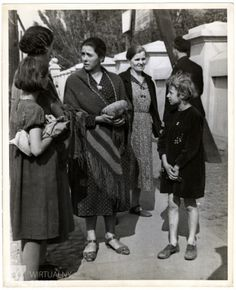 A group of Polish women and children gather on the street during the Siege of Warsaw - the woman in the center is holding a loaf of bread