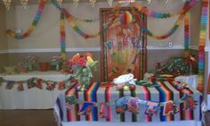 Main table colorfully decorated with Mexican blanket, colorful flowers and banners.