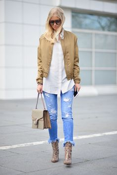 A bomber jacket with a tunic button-up shirt, fringe jeans, and ankle booties