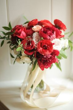 Orchid Dynasty designed this romantic red bouquet, made up of peonies, ranunculi, roses, and greenery. | Photo by Pepper Nix