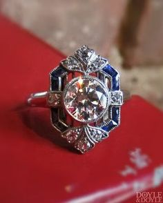 Beautiful geometric design on this Art Deco diamond engagement ring with French cut sapphire accents. Click to see more French cut sapphire and diamond rings!