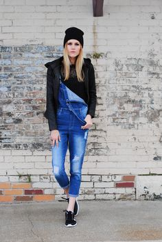 7 ways to spice up a basic black t-shirt - wear a black t-shirt with denim overalls, a leather jacket, black knit beanie, and cool black sneakers
