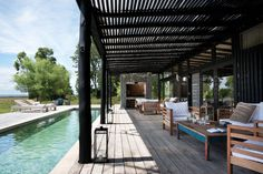 Verano, ¡tiempo de pileta! Acá, una en forma rectangular angosta, acompañada de una gran galería de troncos con espacios de relax.