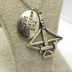 A fantastic piece of the Walking Dead Jewelry, this beautifully crafted piece features a replica of Daryl Dixon's crossbow and a small pendant with The Walking Dead expertly engraved in it's silver fa