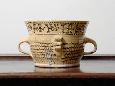 A late 20th century reproduction of a 17th century lead-glazed earthenware slipware posset pot, by John Hudson, Yorkshire